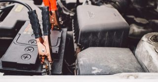 Truck battery getting a jump start with jumper cables in Phoenix
