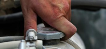 man checking truck radiator coolant level on a semi truck